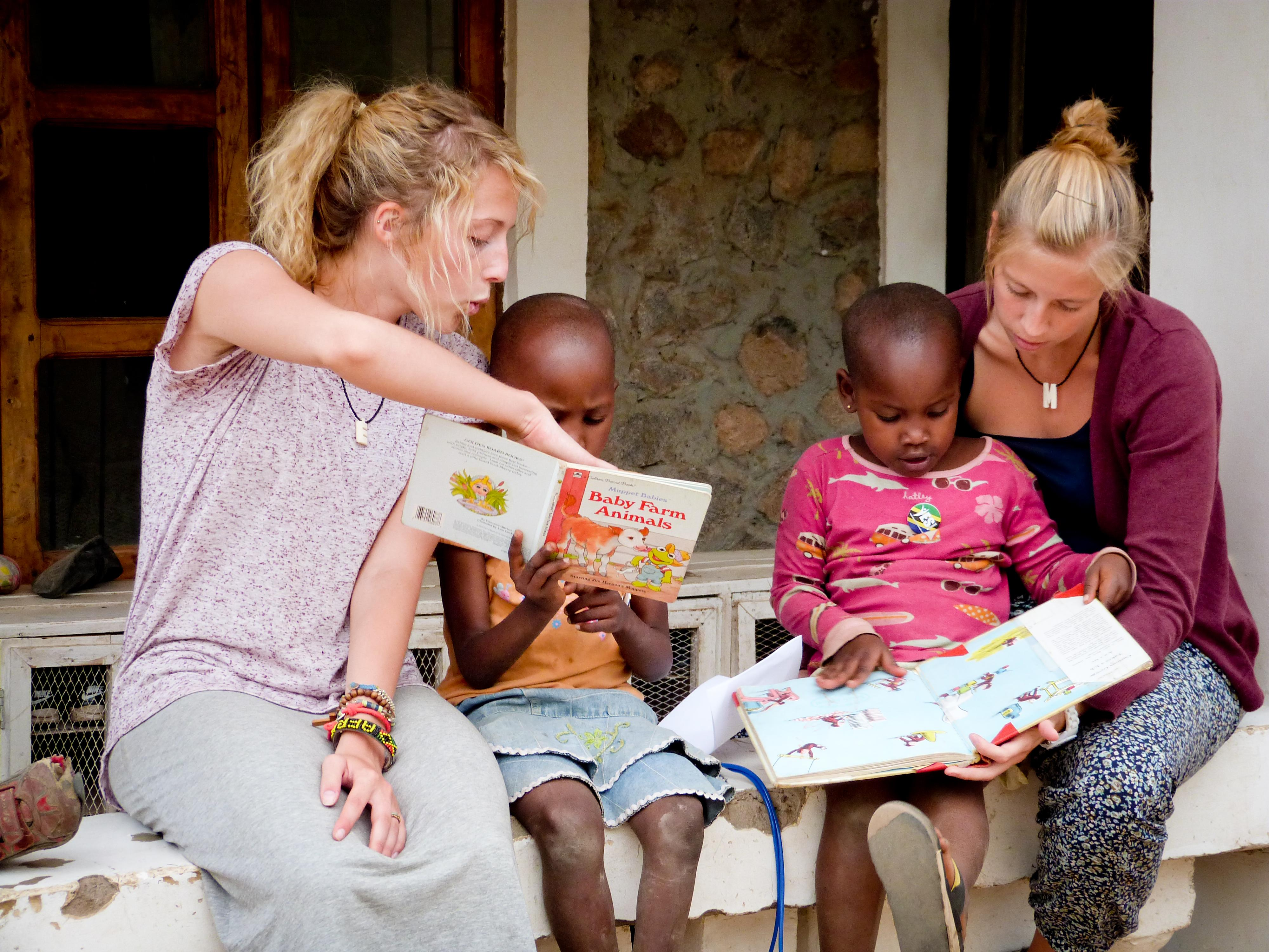 Children read books with Projects Abroad volunteers teaching English in Tanzania
